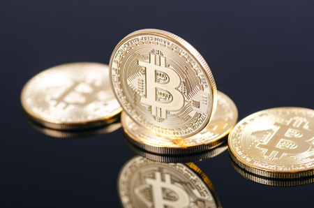 Golden bitcoin coins on a dark background with reflection. Virtual currency. Crypto currency. New virtual money.