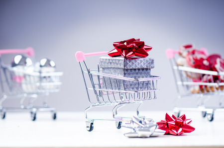 Shopping trolley with christmas gift. Gift box with red ribbon isolated on a white background. Christmas decoration