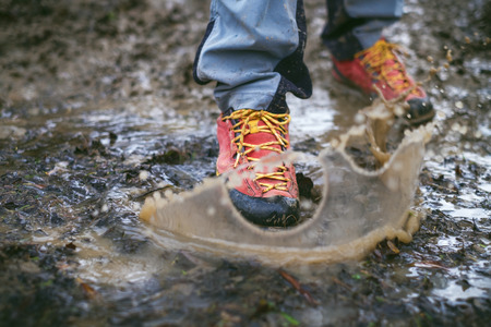 Detail of trekking boots in a mud. Muddy hiking boots and splash of water. Man splashing in muddy and water in the countryside.Detail of trekking boots in a mud. Muddy hiking boots and splash of water. Man splashing in muddy and water in the countryside.
