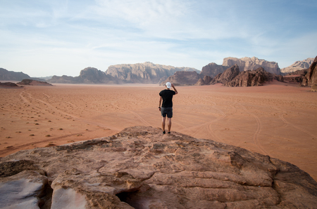Person on a top of mountains in a desert. Sunset view. Nature. Tourist people enjoy a moment in a nature. Wadi rum national park - Jordan Reklamní fotografie