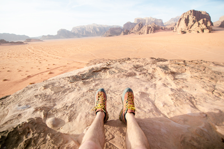 Jordan national park Wadi Rum desert. Beautiful view and panoramatic picture of man legs and outdoor shoes. Natural background. Sunset in a desert