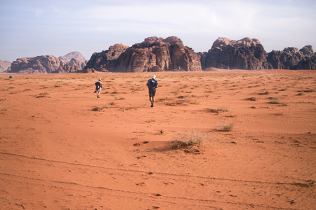 Two hikers in a sand desert. Tourist friends in Jordan natural park Wadi Rum.Group of backpackers walking on the road. Natural background Foto de archivo - 100616350