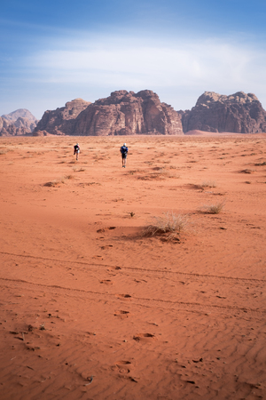 Two hikers in a sand desert. Tourist friends in Jordan natural park Wadi Rum.Group of backpackers walking on the road. Natural background Foto de archivo - 100590810