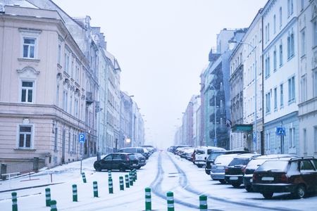 Prague city street under the snow. Cars driving on a blizzard road. Snow calamity in the city. Snow covered cars. Winter Reklamní fotografie
