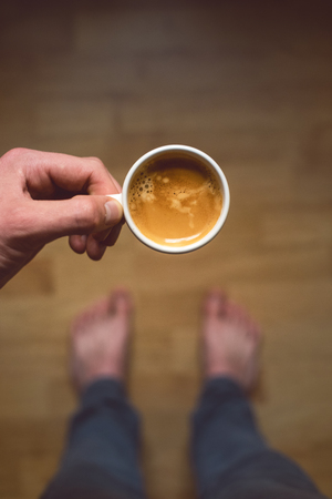 Young man drinking morning coffee and. Coffee break. Man holding cup of fresh roasted coffee. Top view