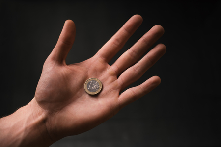 Man holding a coins. Euro currency on a black background. Hand´s of young man holding a money. Finance and banking concept. Black economy. Stok Fotoğraf