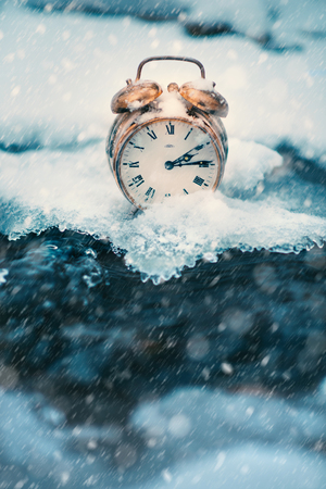 Frozen time. A clock on an ice next to the water. Extreme weather situation. Snow falling on a clock in a nature. Golden old clock. Banco de Imagens