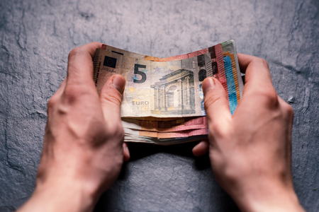Hand´s of young man holding a money. Banknotes on a stone background. Euro money bank notes of different value. European currency - Euro. Bills of money. Man holding a bills of money. Imagens