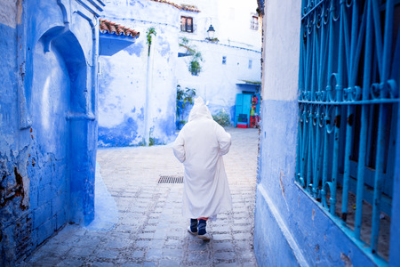Muslim man in tradition maroccan dress walking in blue city called - Chefchaouen.