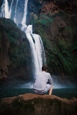 Young man sitting on a stone against Ouzoud waterfalls - Morocco, Africa. Concept of travel.