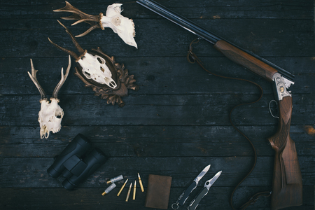 Professional hunters equipment for hunting. Rifle, knives, trophy sculs, ammunition, and others on a wooden black background. Trophy sculs from Roe deer. Reklamní fotografie