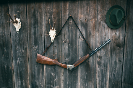 Professional hunters equipment for hunting. Rifle, Deer, Roe deer trophy sculs and others on a wooden black background. Trophy sculs from Roe deer and Deer on the wall.