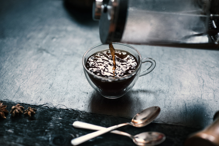 Pouring a coffee from french press to coffee mug on a stone, dark background.