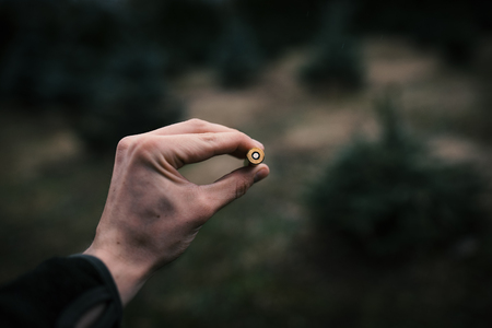 Man´s hand holding an ammunition against natural background. Professional hunter and ammunition for hunting. Caliber 8x57
