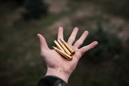 Flying ammunition above a man hand. Professional hunter and ammunition for hunting. Caliber 8x57. Concept of industry. Фото со стока
