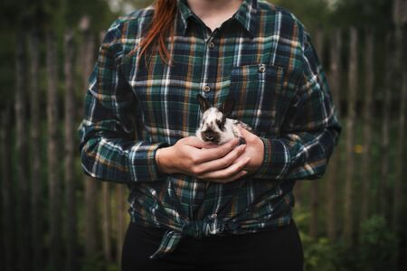 Young woman holding a small, cute bunny. Farmer holding rabbit. Concept of farm and animals. Фото со стока