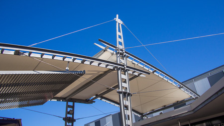 Sail shade pergola made of galvanized steel and stainless steel wire cable tall structure against the blue sky