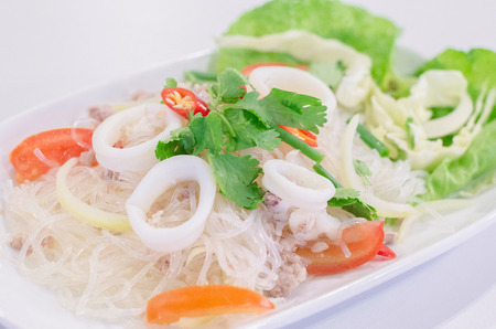 glass noodle salad with white octopus and pork in white dish photo