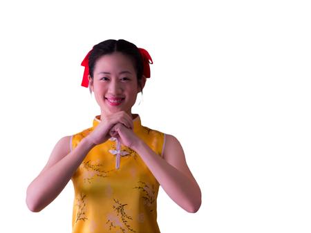 joyfull: Smiling asian girl in yellow cheongsam is respecting
