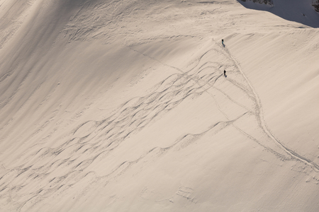 two skier in deep snow driving along traces, far shoot Stockfoto