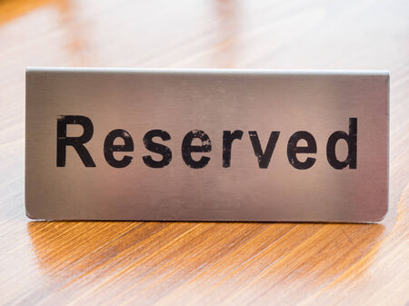booked: close up reserved sign on table