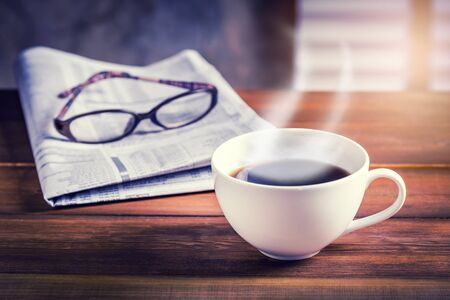 daily life: Coffee cup with newspaper and glasses in background on wooden table. Vintage tone photo with sunlight filter effect.