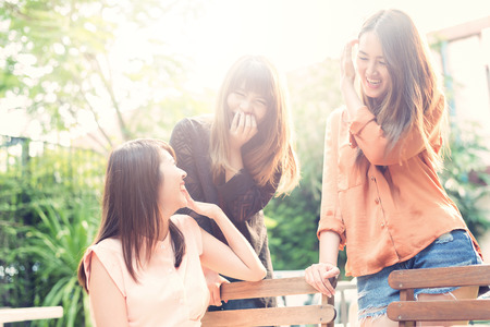 Three beautiful happy Asian girl smile and laugh together.Image with sunlight filter. Stock Photo