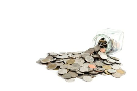 secure growth: Coins spilling out of glass jar on white background. Financial and banking concept