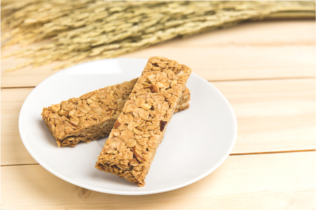 cereal bar: Oatmeal, almond and honey cereal bar on white plate.