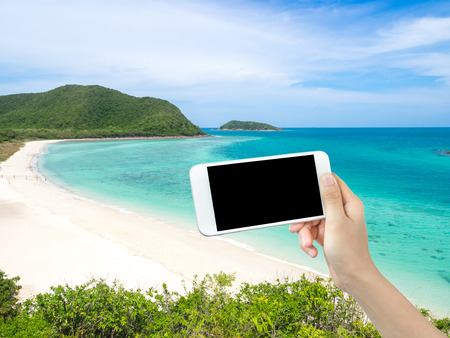 corall: Hand holding blank screen smart phone with beautiful view of white beach sand and the sea in background Stock Photo