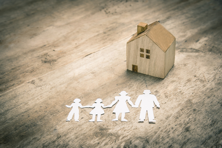 Paper cut family with house on vintage wooden background.