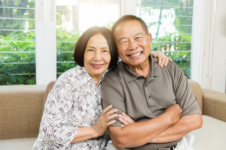 Happy senior Asian couple smiling at home.