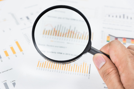 equities: Hand holding magnifying glass analyzing business financial data. Stock Photo