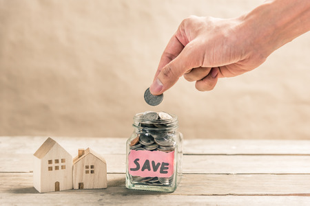 Male Hand Putting Coin In Glass Jar Of Coin For Saving Money For Buying  House Photo