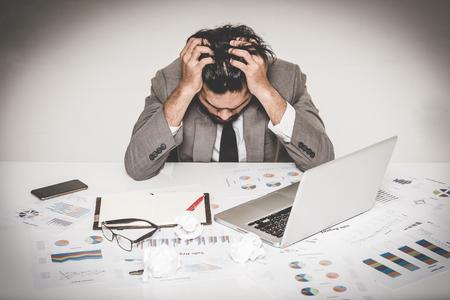 Portret van beklemtoonde zakenman burnout die zijn hoofd met beide hand op het werk houdt