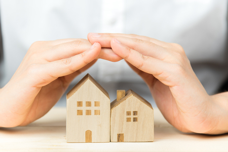 protection hands: Female hand cover wooden house. House protection concept