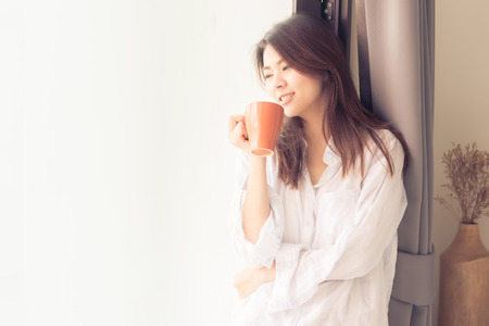 Happy beautiful young Asian woman smile while drinking coffee in morning by window