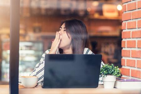 Visto a través de vidrio con reflexiones de la mujer asiática joven de bostezo soñoliento durante el uso de la computadora portátil en el café Foto de archivo - 66218749