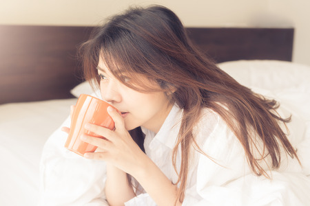 hot asian: Happy beautiful young Asian woman smile while drinking coffee in morning in bed room. Фото со стока