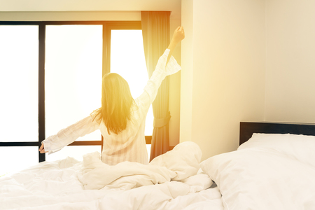 Rear view of woman stretching in bed after wake up in morning with sunlight Stock Photo