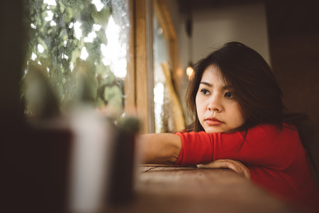 Portrait of lonely young Asian woman looking through a window. Archivio Fotografico