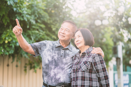 Happy senior Asain couple outdoor with man pointing into distance.Warm tone photo with sunlight.