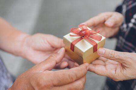 La mano del hombre mayor da una caja de regalo a la mano mayor de la mujer Foto de archivo - 71107386