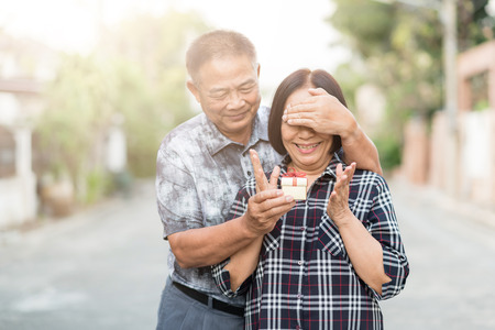 Happy Senior Asian man covering eyes of senior Asian woman for surprise with gift box. Archivio Fotografico