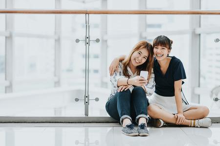 Felices jóvenes asiáticas mejores amigos reír y sonreír mientras se divierten con el teléfono móvil inteligente en interiores. Foto de archivo - 71481479