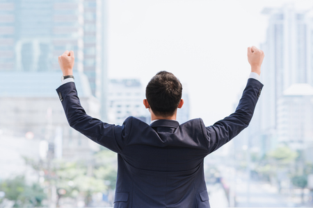 Celebrating success. Back view of excited young Asian businessman arms up while standing outdoors with city  in  background