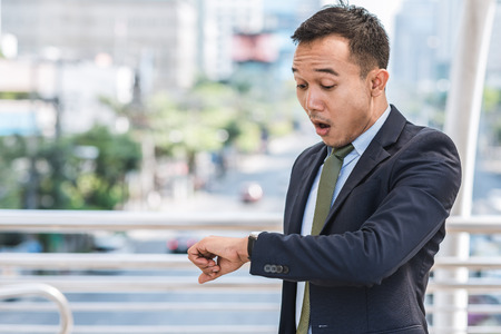 Young Asian businessman shocked while checking time on his watch outdoor in city Banque d'images