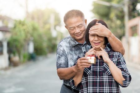 surprise box: Happy Senior Asian man covering eyes of senior Asian woman for surprise with gift box. Stock Photo