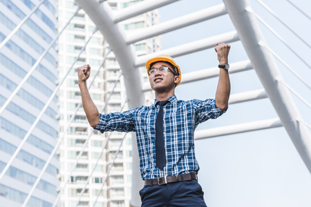 asian architect: Young confident successful Asian engineer or architect raised both arms to celebrate his success with city building in background  Stock Photo