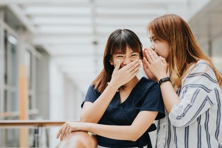ゴシップや笑顔と笑い声で彼女の友人に秘密をささやく若いアジアの女の子 写真素材